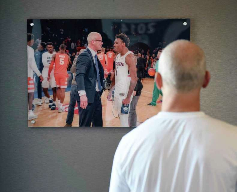 UConn men's basketball coach Dan Hurley looks at a photo in his office from a game against Syracuse before practice at the Werth Family UConn Basketball Champions Center on the UConn main campus in Storrs, Conn. Wednesday, June 9, 2021.
