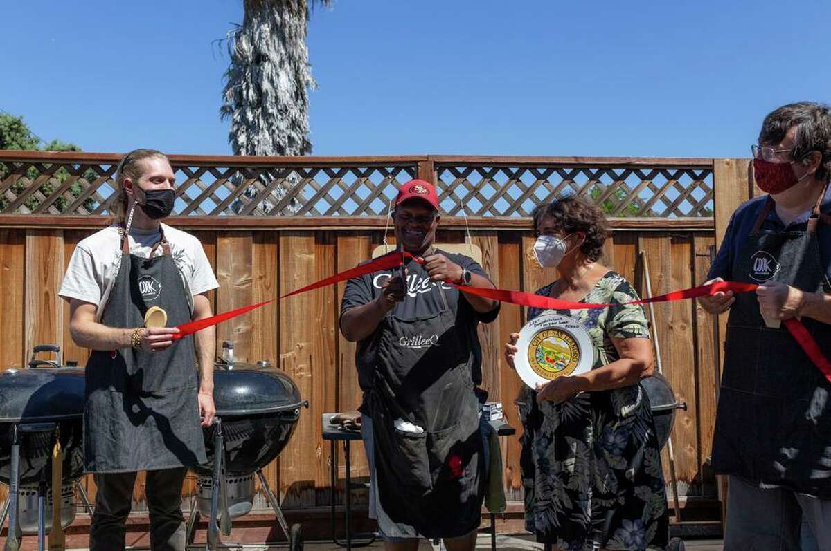 Lee Thomas cuts a red ribbon to mark the grand opening of GrilleeQ as San Leandro Mayor Pauline Russo Cutter (center) and Cook Alliance members Matt Jorgensen (left) and Peter Ruddock (right) look on.