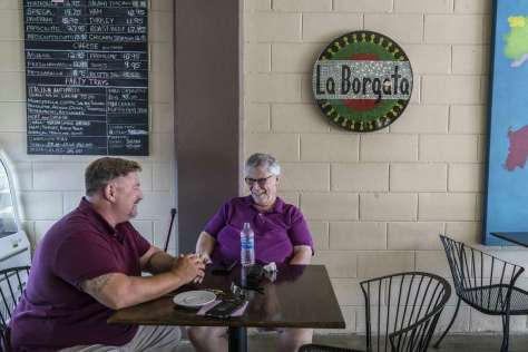 Paulie Spacco (left) and Gregorio Serrao stop in La Borgata Deli in Vacaville. Both are opposed to vaccines and preventive measures such as masks to reduce the spread of the coronavirus.