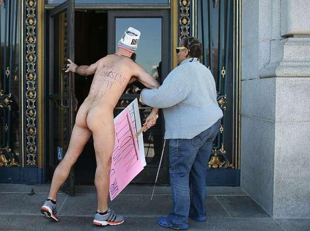 Nude Activist Trey Allen Helps A Blind Woman Through The Front Door At San Francisco City