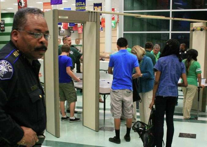 Spring ISD police chief Victor Mitchell watches as students check through metal detectors on the first day of school in 2013. Photo: Provided By Spring High School