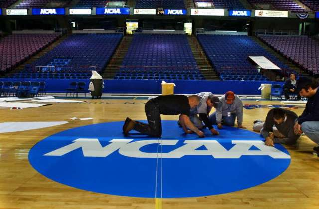 Pepsi Arena employees, from left to right; Jose Soler, Scott Wieczorkowski, Rick Lennox, and Nathan Sims (man at far right is unidentified) apply the finishing touches to a decal applied to center court at the Pepsi Arena on March 26, 2003, in Albany, N.Y., in preparation for the weekend's NCAA East Regional final in men's basketball. The decal has an adhesive, and will be removed at the tournament's end. (Philip Kamrass/Times Union)