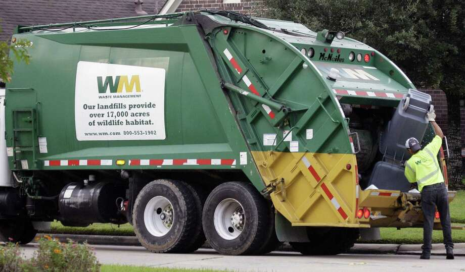 Waste Management workers pick up trash in a Spring, Texas neighborhood. The Houston-based trash giant is acquiring smaller rival Advanced Disposal.  NEXT: See where your trash goes in Houston. Photo: David J. Phillip, STF / AP / AP