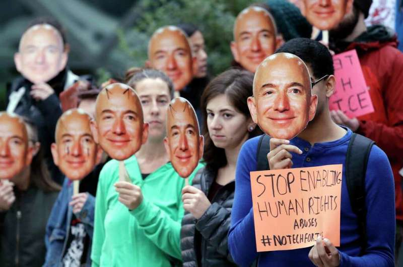 """Demonstrators hold images of Amazon CEO Jeff Bezos near their faces during a Halloween-themed protest at Amazon headquarters over the company's facial recognition system, """"Rekognition,"""" Wednesday, Oct. 31,"""