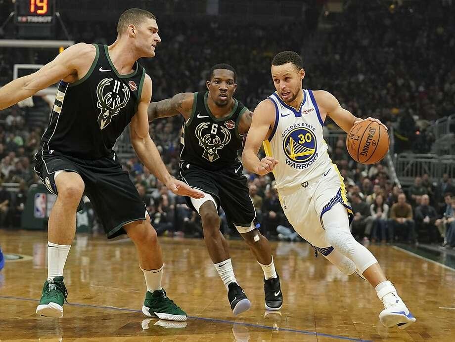 Stephen Curry des Golden State Warriors entraîne Eric Bledsoe et Brook Lopez, des Milwaukee Bucks, au cours de la première moitié d'un match de basket de la NBA, le vendredi 7 décembre 2018 à Milwaukee. (Photo AP / Morry Gash) Photo: Morrry Gash / Associated Press