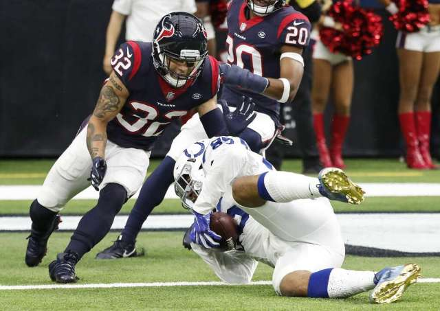<p>Indianapolis Colts tight end Eric Ebron (85) dives under Houston Texans free safety Tyrann Mathieu (32) for a 14-yard touchdown reception during the second quarter of an NFL football game at NRG Stadium on</p>