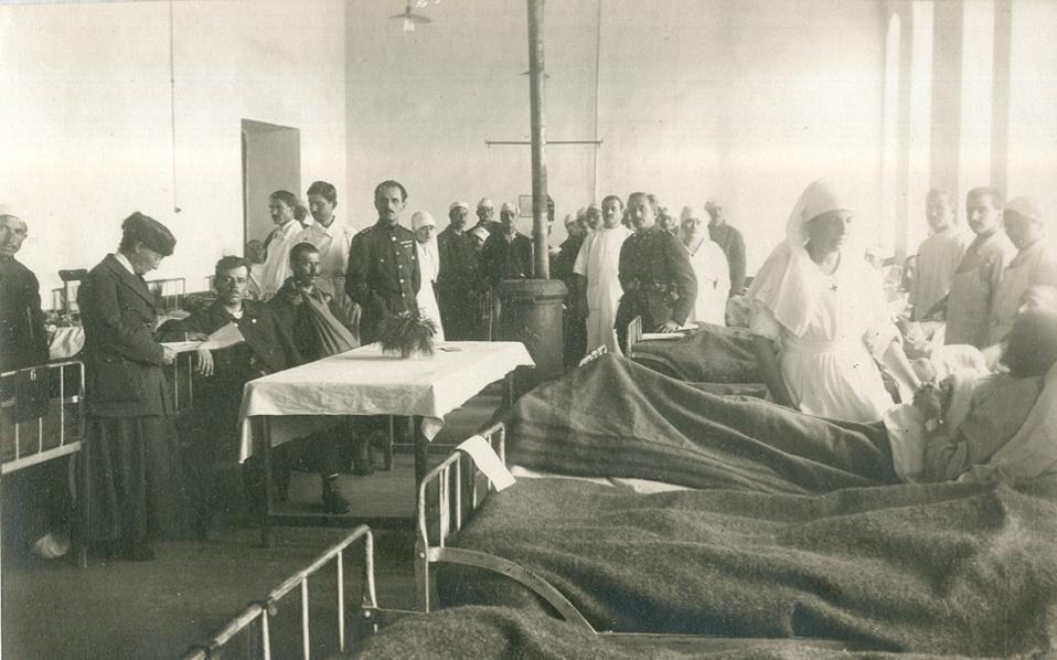 Θάλαμος στρατιωτικού νοσοκομείου με τραυματίες πολέμου. Ορθιος στο βάθος, ένστολος, ο Νικόλαος Σμπαρούνης, ο οποίος υπηρέτησε με το Υγειονομικό Σώμα στο Μακεδονικό Μέτωπο (1918), στην Ουκρανία (1919) και στη Μικρά Ασία (1919-1922).