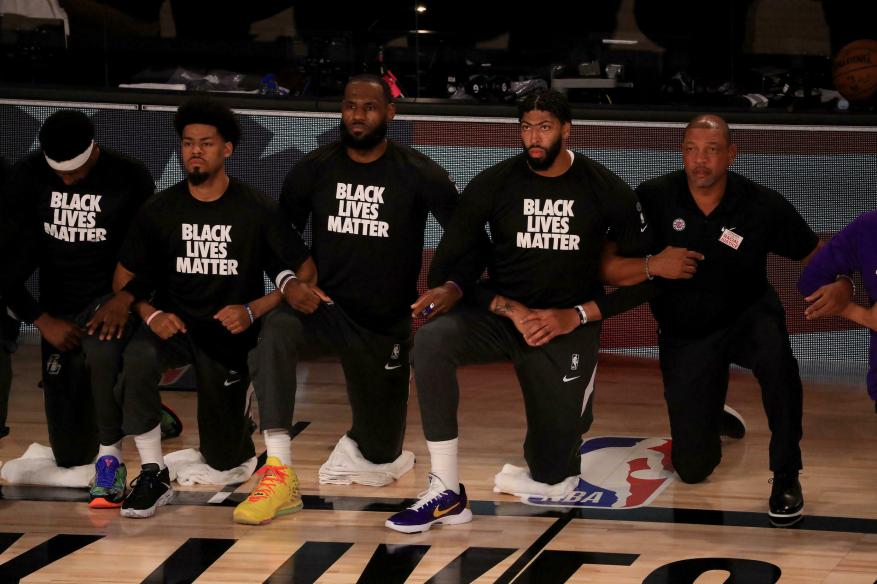 Los Angeles Lakers leaders LeBron James and Anthony Davis kneel down in support of the Black Lives Matter movement alongside teammates and rivals from the Clippers on July 30, 2020 in Lake Buena Vista, Florida.