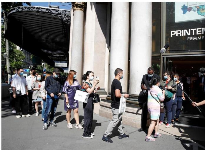 People, wearing face masks, wash their hands with disinfectant before entering the Printemps Haussmann department store in Paris as France gradually eases its lockdown measures and restrictions following the outbreak of the disease in Paris. coronavirus (COVID-19) in France, May 28, 2020.