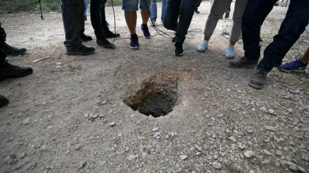 Policías y periodistas se reúnen en torno a un agujero utilizado por seis presos palestinos para escapar de la prisión de Gilboa después de haber cavado un túnel bajo un fregadero.