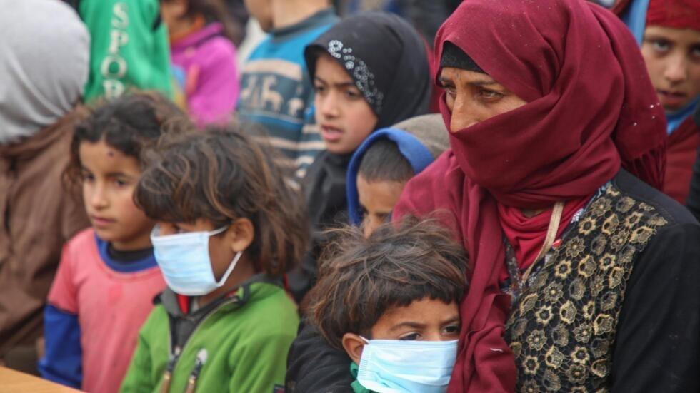 Des Syriens déplacés, certains portant des masques de protection, écoutent des médecins mener une campagne de sensibilisation au nouveau coronavirus, le 18 mars 2020.