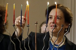 Elena Kagan lighting a Hanukiah