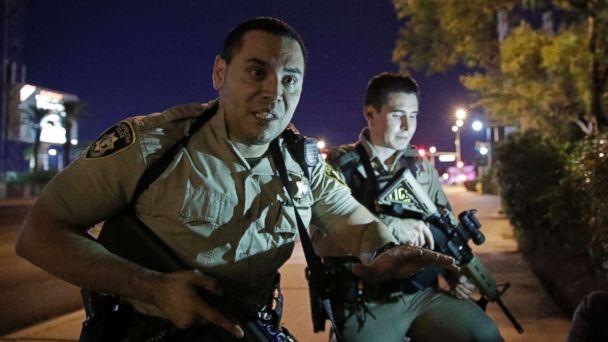 PHOTO: Police officers advise people to take cover near the scene of a shooting near the Mandalay Bay resort and casino on the Las Vegas Strip, Sunday, Oct. 1, 2017, in Las Vegas. (John Locher/AP)