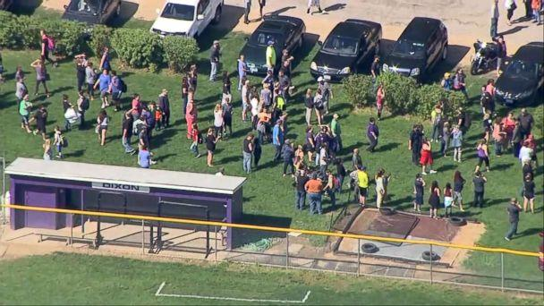 PHOTO: People gather a short distance from Dixon High School in Dixon, Ill., after a police officer confronted and injured an armed man at the school, May 16, 2018. (WLS)