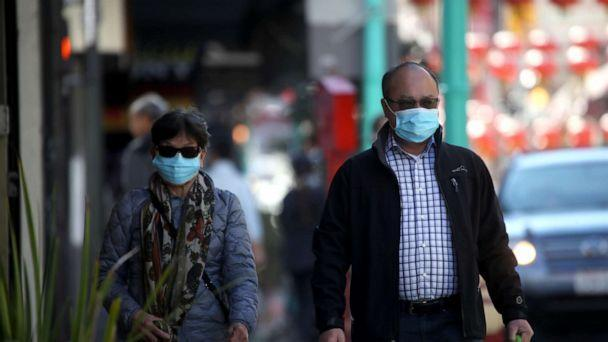 PHOTO: People wear surgical masks as they walk along Chinatown's Grant Avenue in San Francisco, California, on Feb. 26, 2020. (Justin Sullivan/Getty Images)