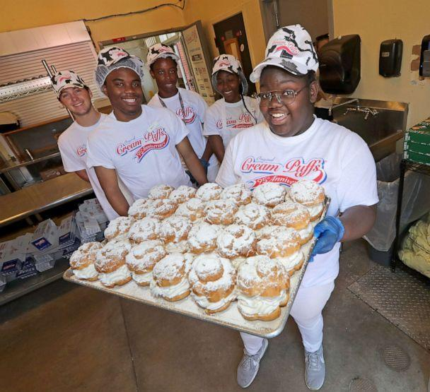 PHOTO: Jahtaya Woolley, a member of the puff cream team, proudly holds a tray of fresh cream with his puff cream teammates at the State Fair Park in West Allis, Wisconsin, July 31, 2019, before the Wisconsin State Fair. (Milwaukee Journal Sentinel via USA Today, FILE)