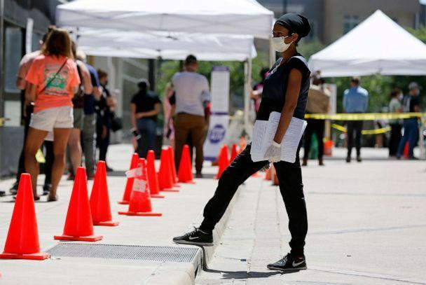 PHOTO: Paramedic Jasmine Lyons handing out documents to people standing in line at the COVID-19 recreational area in Dallas, June 11, 2020. (Tony Gutierrez / AP)