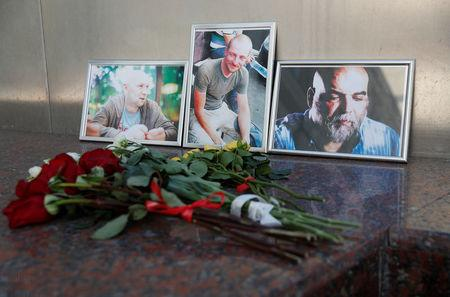 Photographs of journalists, (R-L) Orhan Dzhemal, Kirill Radchenko and Alexander Rastorguyev, who were recently killed in Central African Republic by unidentified assailants, are on display outside the Central House of Journalists in Moscow, Russia August 1, 2018. REUTERS/Maxim Shemetov