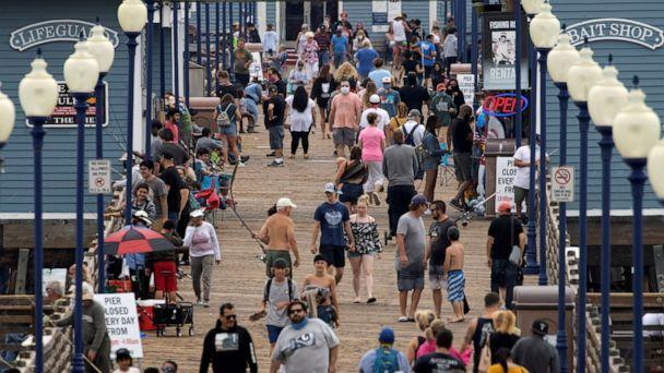 PHOTO: Few people wear masks as they walk on the beach pier in Oceanside, Calif., June 22, 2020. (Mike Blake/Reuters)