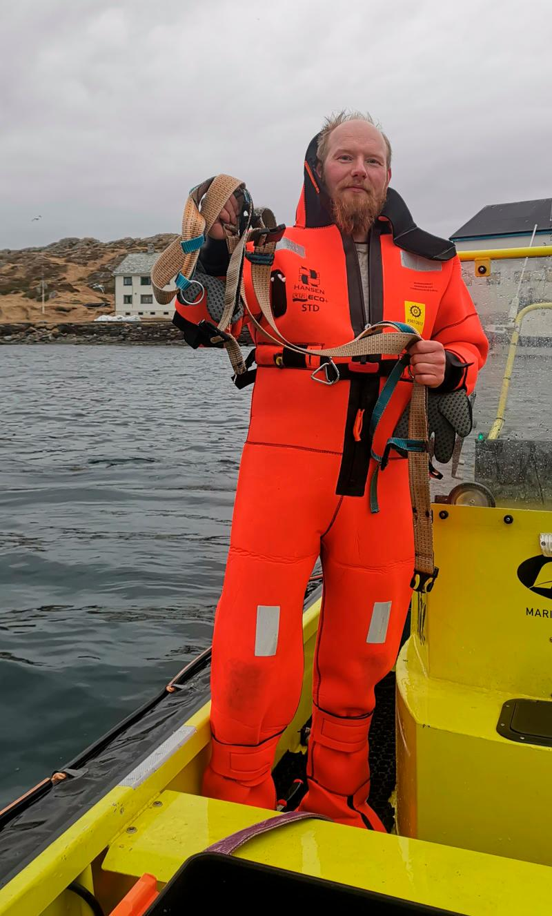 "Norwegian Joergen Ree Wiig holds the whale harness after it was removed from a beluga whale off the northern Norwegian coast Friday, April 26, 2019. The harness strap which features a mount for an action camera, says ""Equipment St. Petersburg"" which has prompted speculation that the animal may have escaped from a Russian military facility. (Joergen Ree Wiig/Norwegian Direcorate of Fisheries Sea Surveillance Unit via AP)"