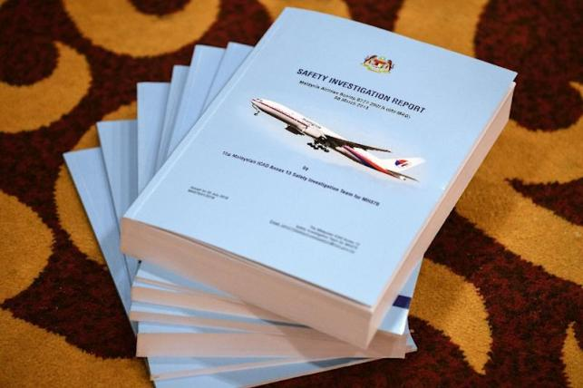 Copies of the MH370 safety investigations report are seen on the floor during a media briefing (AFP Photo/Mohd RASFAN)