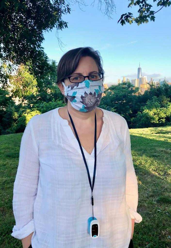 The author, masked and with her oximeter around her neck, on a walk in her Jersey City neighborhood with the Freedom Tower in the background in June 2020. (Photo: Courtesy of Ann E. Wallace)