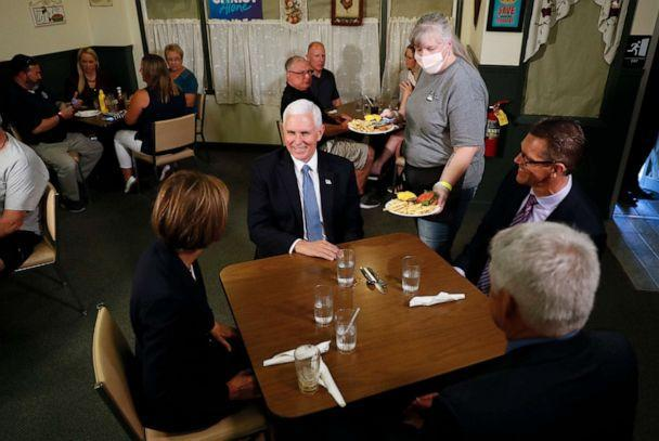 PHOTO: Vice President Mike Pence talks with Iowa Governor Kim Reynolds (left), her husband Kevin and State Senator Randy Fenstroy (right) during a lunch break in Sally, June 16, 2020, in Forest City, Iowa. (Charlie Neibergall / AP)