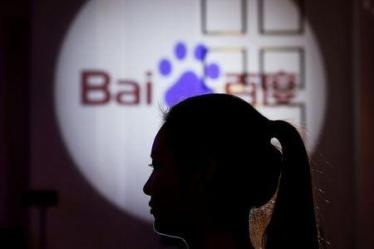 FILE PHOTO: A woman is silhouetted against the Baidu logo at a new product launch from Baidu, in Shanghai, China