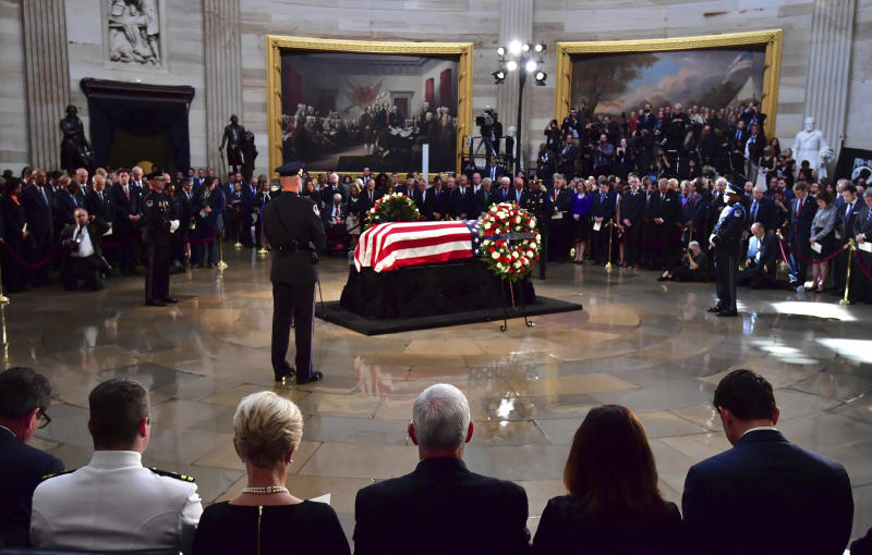 The flag-draped casket of Sen. John McCain, R-Ariz., lies in state at the U.S. Capitol, Friday, August 31, 2018 in Washington. Seated third from left is Cindy McCain and Vice President Mike Pence to her right. (Kevin Dietsch/Pool photo via AP)