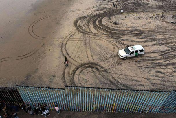 PHOTO: An aerial view of migrants who form part of the Central American migrant caravan being detained and escorted by a border patrol agent after crossing the US-Mexico border fence in Playas de Tijuana, Baja California state, Mexico, Dec. 9, 2018. (Guillermo Arias/AFP/Getty Images)