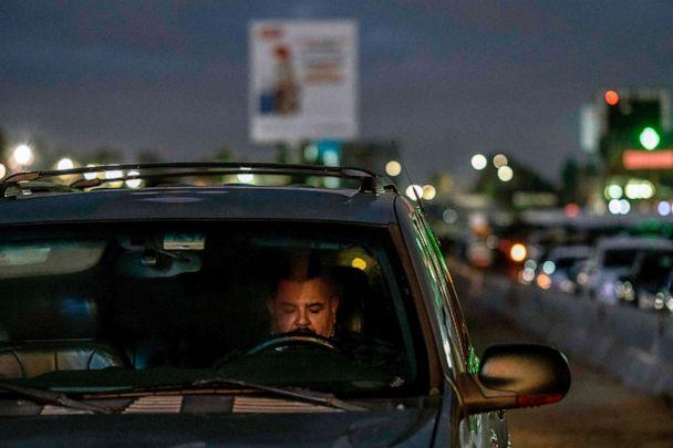 PHOTO: Commuters line up while waiting for the Otay Mesa Port of Entry to open to cross to the United States from Tijuana, Baja California state, Mexico, early May 20, 2020. (Guillermo Arias/AFP via Getty Images)
