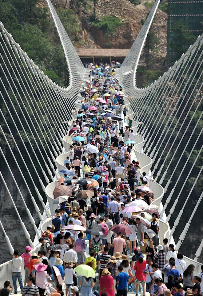 <p>8,000 tourists queued overnight before Saturday's trial opening to be the first to step onto the Zhangjiajie Grand Canyon's glass-bottomed bridge. (Getty Images)<br /></p>