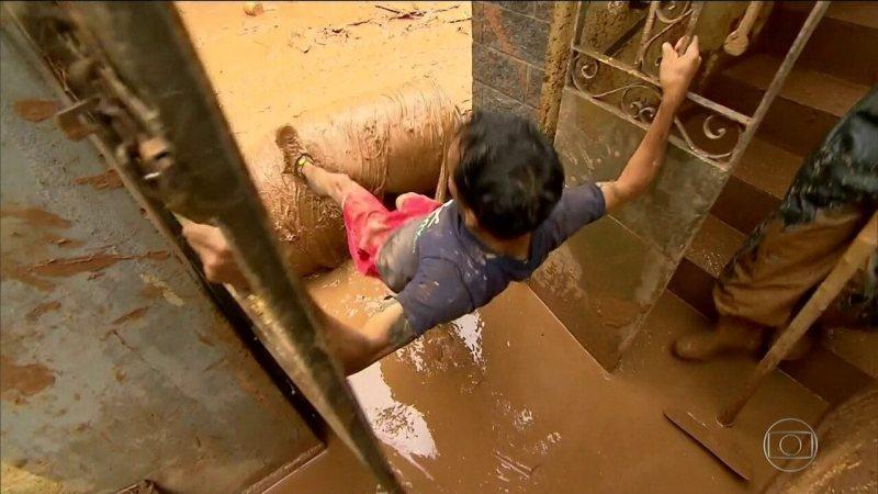 Pintor se arrisca em contato com a lama em cidade de MG