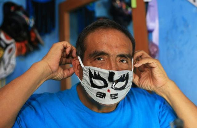 Jose Isaias Huerta tries on one of the masks he manufactured in Puebla, Mexico