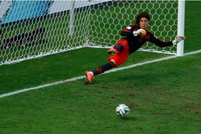 Mexico's Ochoa is sent the wrong way as Huntelaar of the Netherlands scores their penalty during their 2014 World Cup round of 16 game at the Castelao arena in Fortaleza