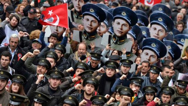 Members of the nationalist Youth Union of Turkey (TGB) wearing military caps shout slogans while holding portraits of Mustafa Fehmi Kubilay during a rally commemorating the death of Kubilay in Ankara