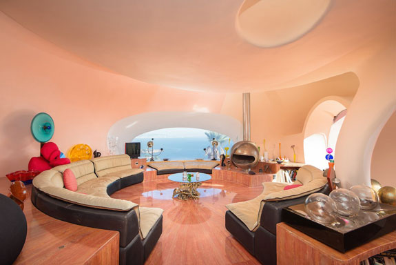 the-living-room-has-a-space-age-themed-decor-echoing-the-saucer-like-shape-of-the-bubbles-that-make-up-the-home-even-the-sofa-is-round