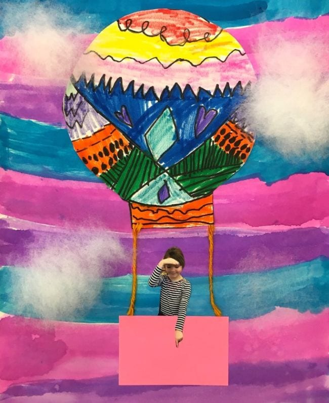 Brightly-patterned paper hot air balloon on a marker-striped background with the photograph of a child in the basket