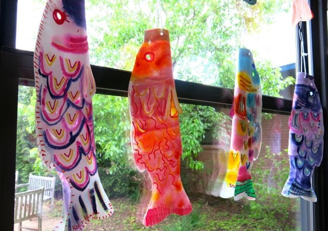 Colorful fish-shaped kites hanging in a window