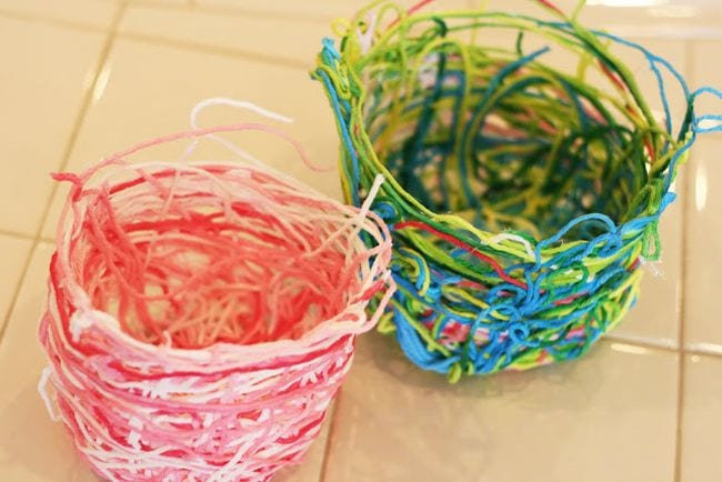 Small baskets made of colorful yarn stiffened with glue (First Grade Art)