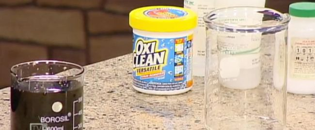 Container of OxiClean with beakers of liquid on a counter (Eighth Grade Science)