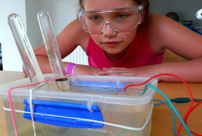 Eighth grade girl wearing goggles, looking at a container of water with test tubes and electric wires