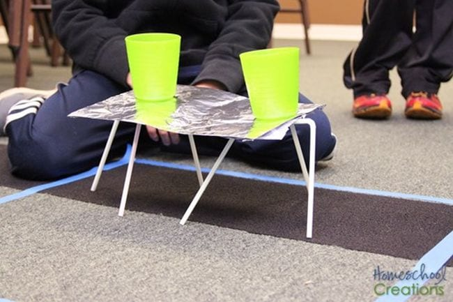 Student showing a foil platform balanced on drinking straws, holding two yellow plastic cups of water