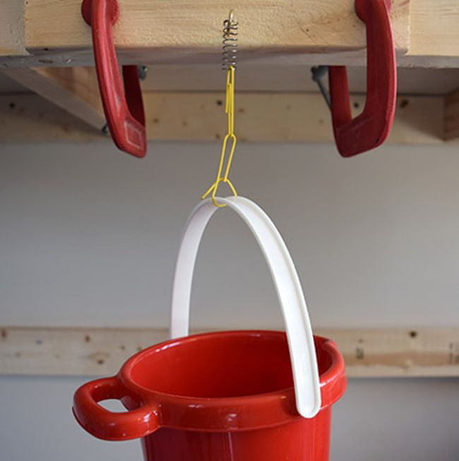 Red plastic bucket suspended by several paper clips from a spring on a hook (Eighth Grade Science)
