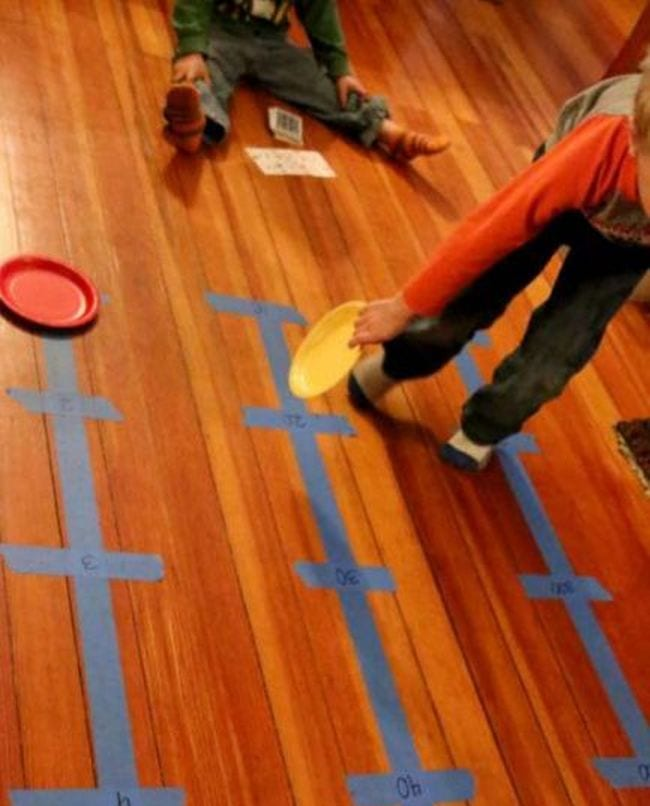 Young student moving colorful paper plates along number lines made from blue painter's tape on the floor