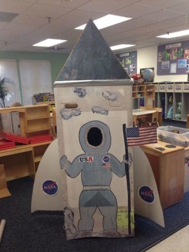 White and grey replica of NASA space shuttle with astronaut face cutout