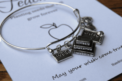 Books and subjects silver charm bracelet on paper note