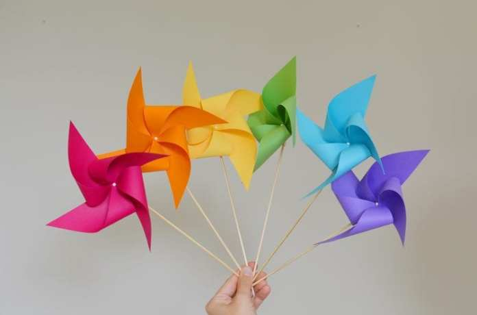 a hand holding up six colorful pinwheels