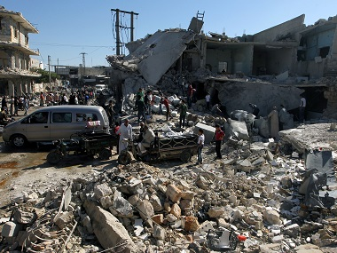 People gather at a site hit by airstrikes in the rebel-held town of Atareb in Aleppo province, Syria, 25 July, 2016. Reuters
