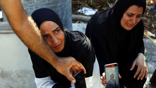 Zeinab Zer Eldin, left, and her sister-in-law shows a photo of her missing husband near the site of the explosion in the port of Beirut, Lebanon. AP